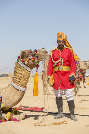 village man: JAISALMER, INDIA - FEBRUARY 09, 2017 : Camel and indian men wearing traditional Rajasthani dress participate in Mr. Desert contest as part of Desert Festival in Jaisalmer, Rajasthan, India