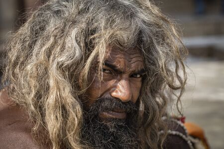 VARANASI, INDIA - JANUARY 26, 2017 : Portrait of Shaiva sadhu, holy man on the ghats of the Ganges river in Varanasi, India . Close up