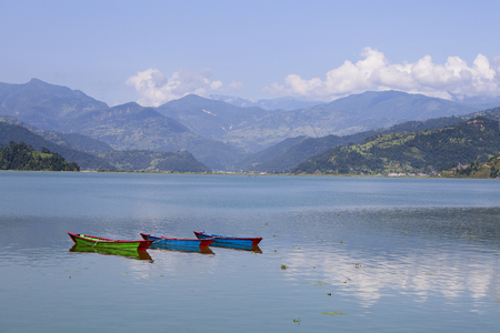 phewa: Lake Phewa, wooden boat in Pokhara, Nepal, with the Himalayan mountains in the background Stock Photo