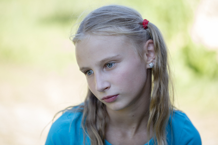 yearning: Portrait of a sad girl young girl outdoors, close up Stock Photo