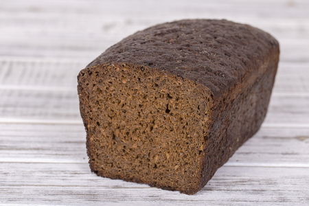 A loaf of rye bread on white wooden background, close up
