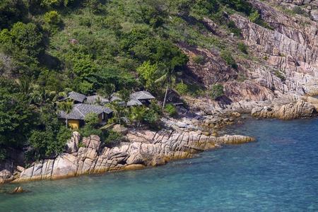 bungalows tropical en una playa rocosa al lado del agua de mar azul. La isla de Koh Phangan, Tailandia