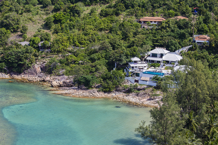 Tropical bungalow on a rocky beach next to the blue sea water. Koh Phangan Island, Thailand