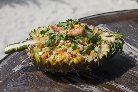 Cooked brown rice with vegetables and tofu in a pineapple, close up