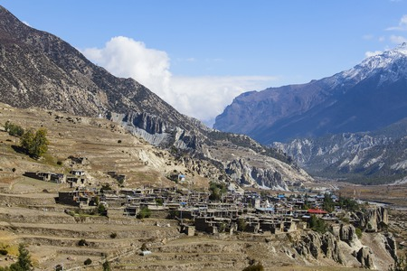 build in: Traditional stone build village of Manang. Mountains in the background. Annapurna region, Nepal. Sunny day of Nepal summer. Big mountain, stone houses, blue river and fresh air. Eco travel