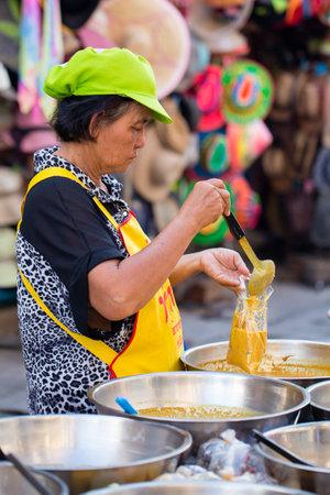 sell: KOH PHANGAN, THAILAND - NOVEMBER 26, 2016 : Thai street vendor woman prepares and sells food on the traditional street market in Koh Phangan, Thailand