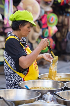 KOH PHANGAN, THAILAND - NOVEMBER 26, 2016 : Thai street vendor woman prepares and sells food on the traditional street market in Koh Phangan, Thailand