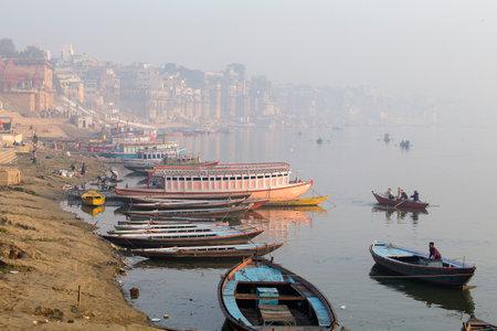 VARANASI, INDIA - JANUARY 25, 2017 : Morning view at holy ghats and wooden boats at the river ganges of Varanasi, India
