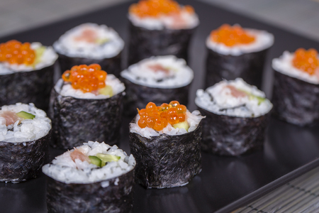Sushi roll with salmon, cucumber, avocado, red caviar. Sushi menu. Japanese food. Close up, on bamboo napkin Stock Photo