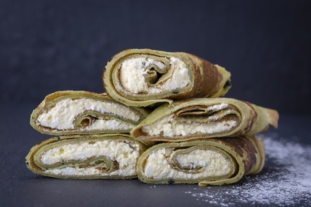 Ukrainian and Russian dishes - homemade pancakes with green spirulina stuffed white cottage cheese with raisins on a black slate background, close up Stock Photo