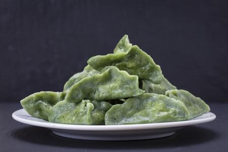 緑の点心、中華料理。牛肉肉、マッシュ ポテトまたは黒いスレート背景にスピルリナとともに、生地にカッテージ チーズとおいしい自家製餃子をク