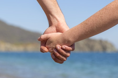 Couple hands held together on a natural sea background, close up