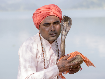 POKHARA, NEPAL - OCTOBER 07, 2016 : Portrait of snake charmer adult man in turban and cobra sitting near the lake Editorial