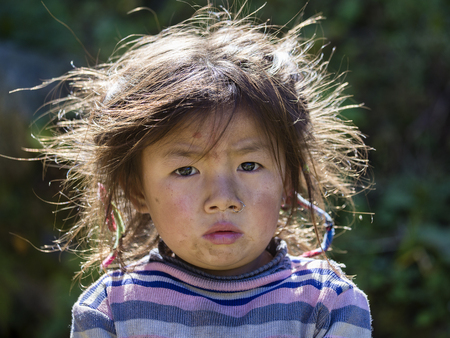 HIMALAYAS, ANNAPURNA REGION, NEPAL - OCTOBER 14, 2016 : Portrait nepalese child on the street in Himalayan village, Nepal Editorial