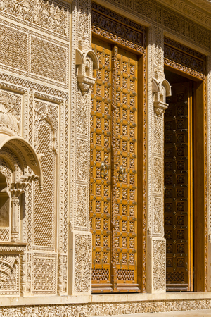 Wooden door and ornament on wall of palace in Jaisalmer fort, India. Close up