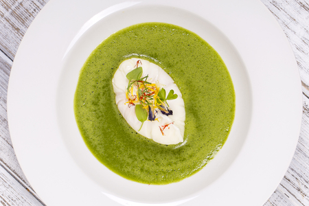 Cooking with local ingredients - poached egg, green healthy soup, close up in white plate