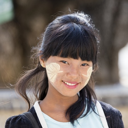 MANDALAY, MYANMAR - JANUARY 16, 2016: Unidentified young Myanmar girl with thanaka on her smile face is happiness. Thanaka is a yellowish-white cosmetic paste made from ground bark.