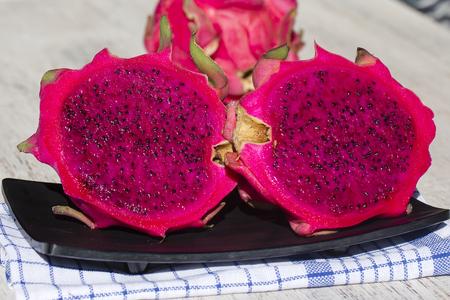 Ripe red pitahaya fruit with half. Dragon fruit . Island Bali, Ubud, Indonesia. Close up Stock Photo