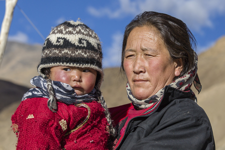 LEH, LADAKH, INDIA - SEPTEMBER 09, 2014: Unidentified local woman with child, outdoor in Ladakh. The majority of the local population are descendant of Tibetan