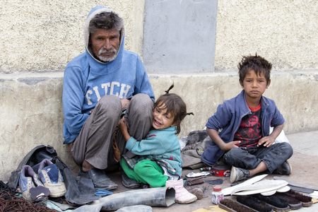 LEH, LADAKH, INDIA - SEPTEMBER 08, 2014: Unidentified beggar family begs for money from a passerby in Leh. Poverty is a major issue in India