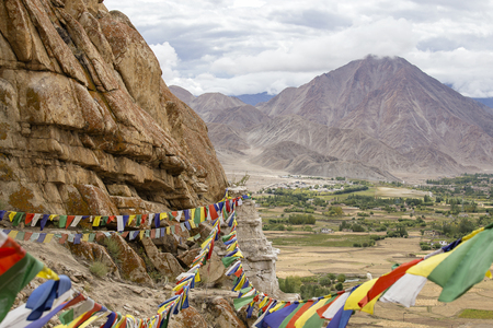 Himalayan mountains and colorful Buddhist prayer flags on the stupa near Buddhist monastery in Ladakh, Jammu Kashmir, India