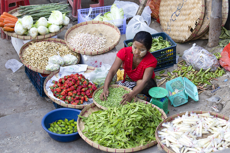 YANGON, MYANMAR - JANUARY 09, 2016: Unidentified woman sell fruit and vegetable on the street food market in the city center, Yangon, Burma, Myanmar