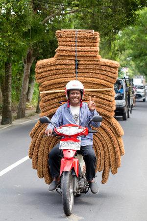 UBUD, BALI, INDONESIA - JANUARY 13, 2018 : Unidentified man is transporting goods on a motorbike on a street in Ubud, island Bali, Indonesia, close up