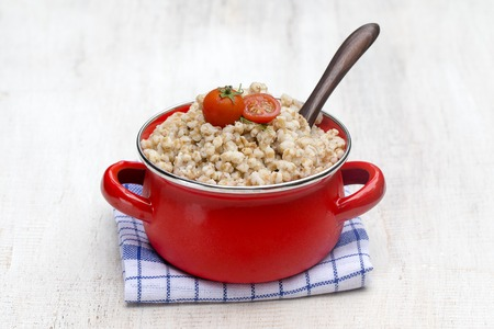 Red pan with boiled wheat porridge - traditional meal in Ukraine, Belarus and Russia. Close up Stock Photo