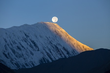 Beautiful landscape in Himalayas, Annapurna region, Nepal. Full moon during a sunrise on the background of snow-capped mountains Standard-Bild - 93727185