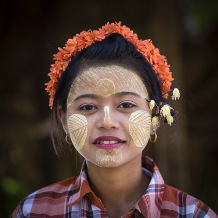 MANDALAY, MYANMAR - JANUARY 17, 2016: A Burmese young girl with thanaka paste on her face in Mandalay, Burma. Thanaka is a yellowish-white cosmetic paste made from ground bark. Editorial