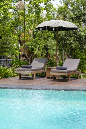 Stock Photo   Swimming Pool, Blue Water, Green Leaves Of Trees And Deck Chairs  In Tropical Garden. Island Bali, Ubud, Indonesia