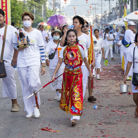 PHUKET, THAILAND - OCT 17, 2015 : Unknown woman using sharp objects to pierce through body to show spiritual strength during a street procession in Vegetarian Festival at Phuket Town, Thailand