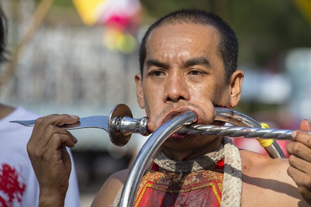 PHUKET, THAILAND - OCT 17, 2015 : Unknown man using sharp objects to pierce through body to show spiritual strength during a street procession in Vegetarian Festival at Phuket Town, Thailand Editorial