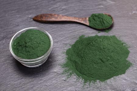 Het organische groene poeder van spirulinaalgen op de zwarte achtergrond van de leischotel, sluit omhoog