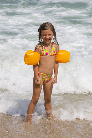 Happy child on the beach in the waves during summer vacation on exotic tropical beach. Holiday on ocean coast for family with young children. Little girl play at the sea