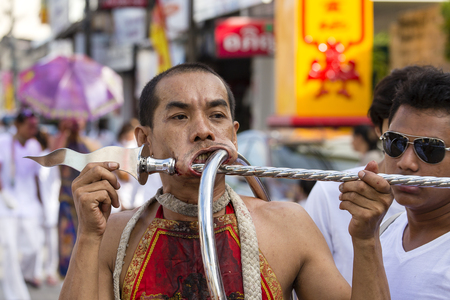 PHUKET, THAILAND - OCT 17, 2015 : Unknown man using sharp objects to pierce through body to show spiritual strength during a street procession in Vegetarian Festival at Phuket Town, Thailand