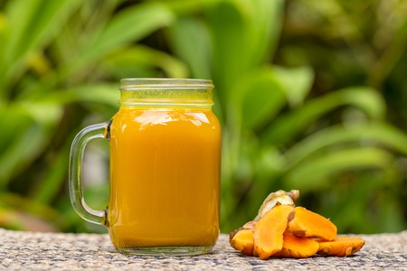 Energy tonic drink with turmeric, ginger, lemon and honey in glass mug, nature background, close up