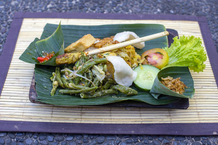 Nasi Campur Bali. A popular Balinese meal of rice with variety of side dishes which are served together with the rice and more as optional extras. Close up. Asian food, Ubud, Bali, Indonesia. Фото со стока