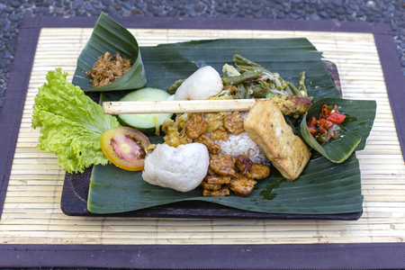 Nasi Campur Bali. A popular Balinese meal of rice with variety of side dishes which are served together with the rice and more as optional extras. Close up. Asian food, Ubud, Bali, Indonesia. Фото со стока - 99487984