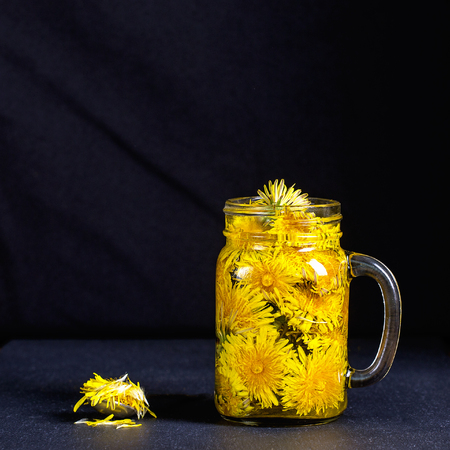 Dandelion yellow flower tea drink in glass mug on black background, close up. Concept of healthy eating Stock Photo