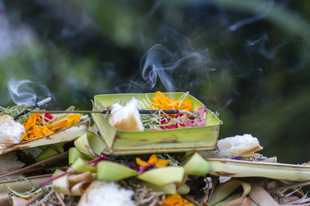 Burning incense sticks surrounded with Balinese offerings outside on a hindu temple in Ubud, Bali, Indonesia. Close up