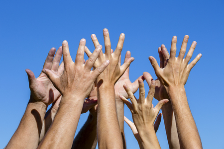 Group of people pulling hands in the air in sunlight. Many hands against blue sky background, close up Stock Photo - 102000706