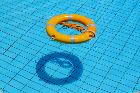 Lifebuoy floating on top of sunny blue water in swimming pool, close up Stock Photo