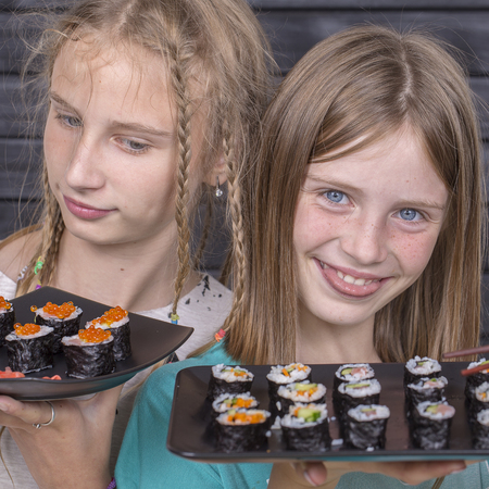 Two teen girl with sushi roll close up portrait, teenage girls eating japanese sushi