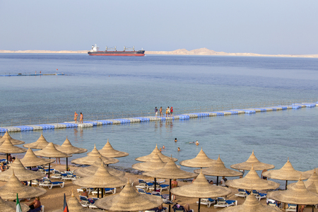 SHARM EL-SHEIKH, EGYPT - MAY 25, 2018: People rest on the beach near red sea in resort hotel, Sharm El Sheikh, Egypt