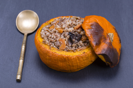 Tasty autumn stuffed pumpkin with buckwheat, carrot, onion, garlic and prunes on the background of black slate , close up
