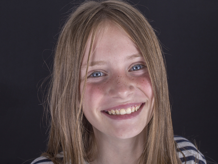 Beautiful blond young girl with freckles indoors on a black background, close up portrait Standard-Bild