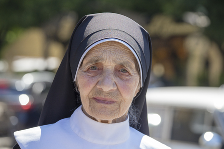 LVIV, UKRAINE - JULY 05, 2018 : Portrait old nun in black and white clothes on the street in the city center Lviv, Ukraine. Close up