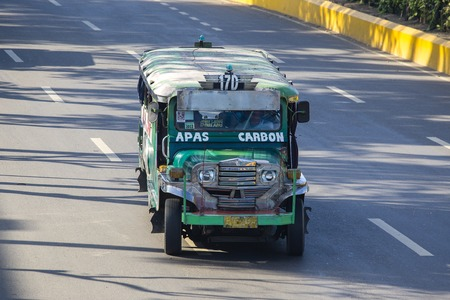 CEBU, PHILIPPINES - MARCH 15, 2014: Jeepneys passing on the street, Filipino inexpensive bus service. Jeepneys are the most popular means of public transportation in the Philippines Editorial