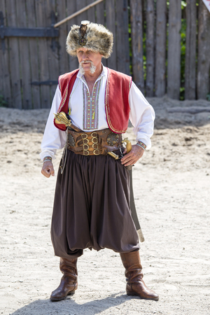 KHORTYTSIA, UKRAINE - JUNE 22, 2013 : Cossack festival at the Zaporozhye Sech in island Khortytsia, Ukraine. Traditional clothes of Cossack man Редакционное